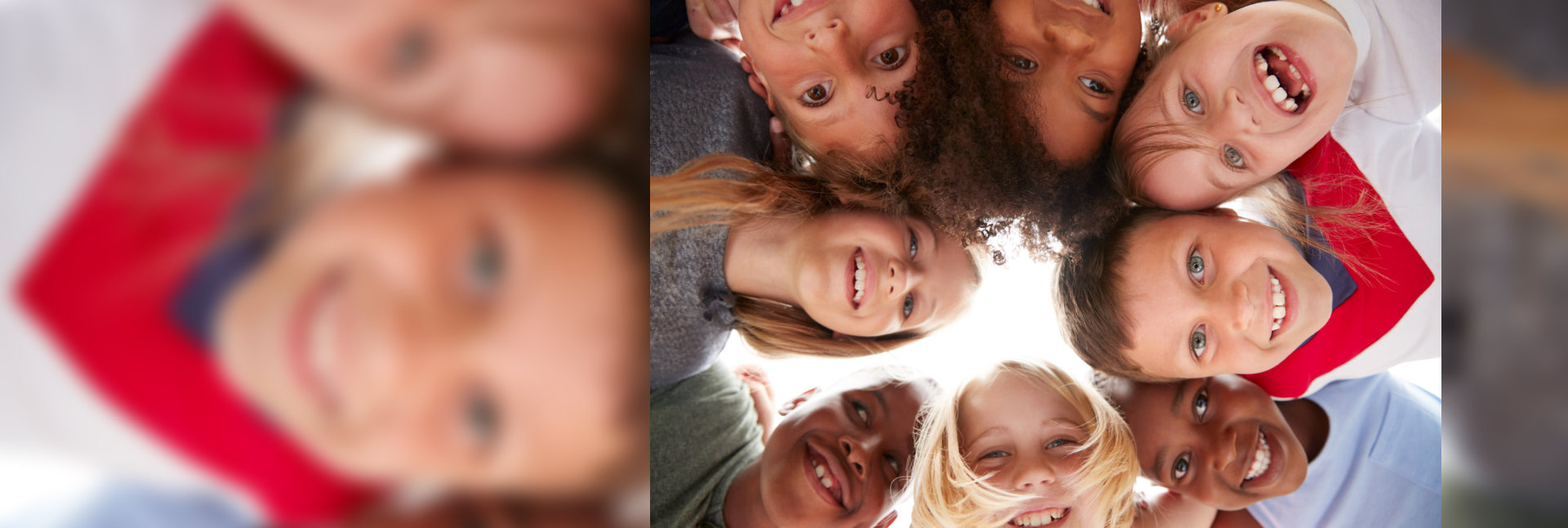 Group Of Multi-Cultural Children With Friends Looking Down Into Camera.